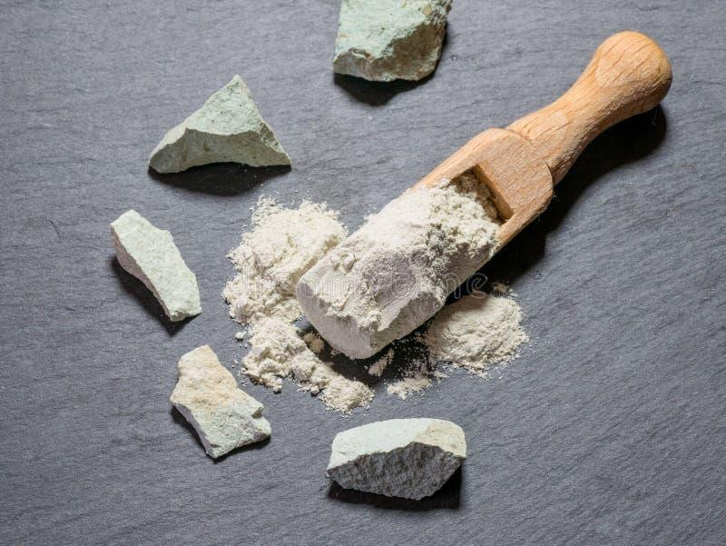 Natürliche rohe Steine und Pulver des Zeoliths auf schwarzem Stein-backgroun stockfotografie