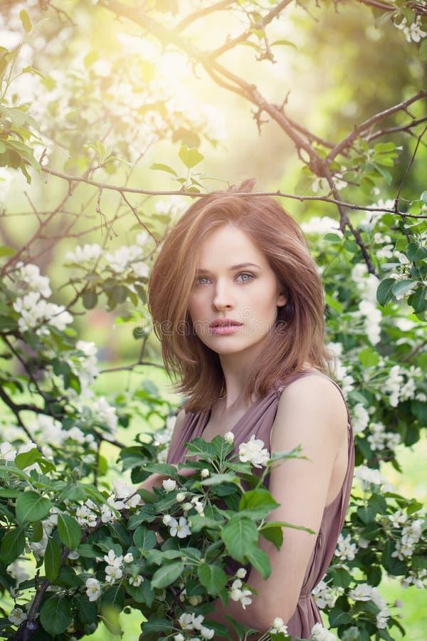 Natürliche Schönheit Schönes weibliches vorbildliches Mädchen mit braunem Blütenpark des Haares im Frühjahr Junge perfekte Frau a lizenzfreie stockbilder