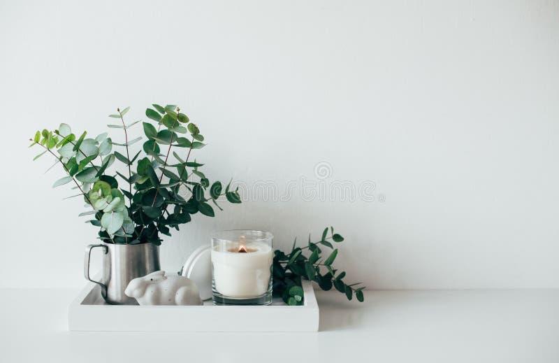 Natürlicher Öko-Haus-Dekor mit Grünblättern und brennender Kerze auf t stockfotografie