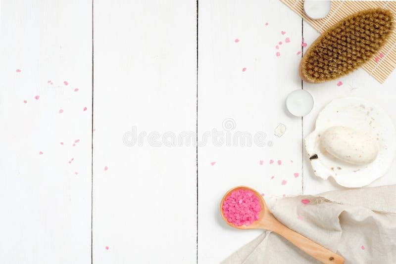 Natürlicher Badekurort, Wellness oder Hautpflegezusammensetzung mit Löffel des rosa Badesalzes, Körperbürste, organische Seife, T stockfotos