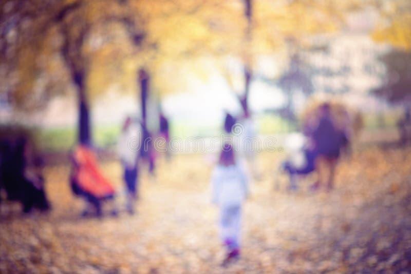 Natürlicher bokeh Hintergrund von den Leuten, die in einen Herbst gehen, parken lizenzfreies stockbild