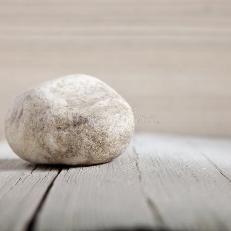 Natürlicher kleiner verwitterter Felsen auf Holz lizenzfreies stockbild