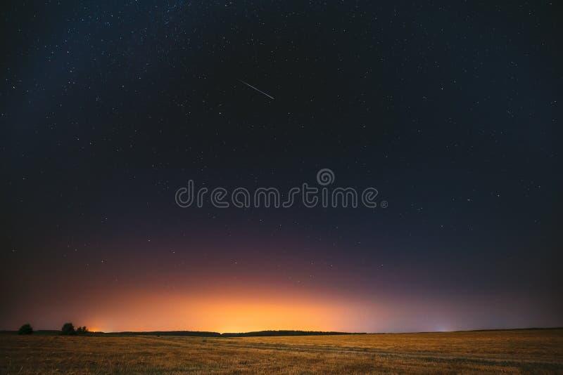 Natürlicher Nachtsternenklarer Himmel-oben genannte Feld-Wiese Glühende Sterne, Meteorit lizenzfreies stockfoto