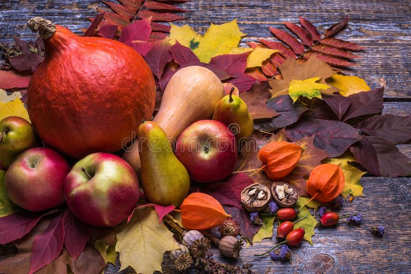 Natürlicher organischer Gemüsekürbis mit reifen Äpfeln und Birnen mit trockenem buntem Blatt auf einem hölzernen Hintergrund stockbild