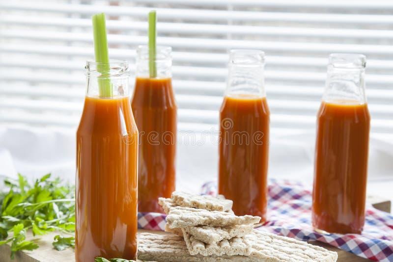 Natürlicher und frischer Karottensaft in den kleinen Flaschen mit frischem Sellerie und einfachem Roggen backt zusammen stockbilder