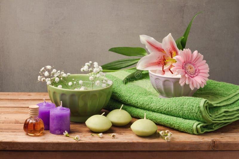 Natürliches Badekurort- und Wellnesskonzept mit frischem Tuch, Kerzen und Blumen auf Holztisch über rustikalem grauem Hintergrund lizenzfreie stockbilder