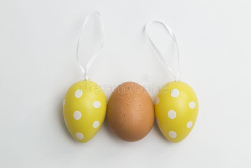Natürliches braunes Ei und zwei künstliche Plastikeier Ostern lizenzfreie stockfotos