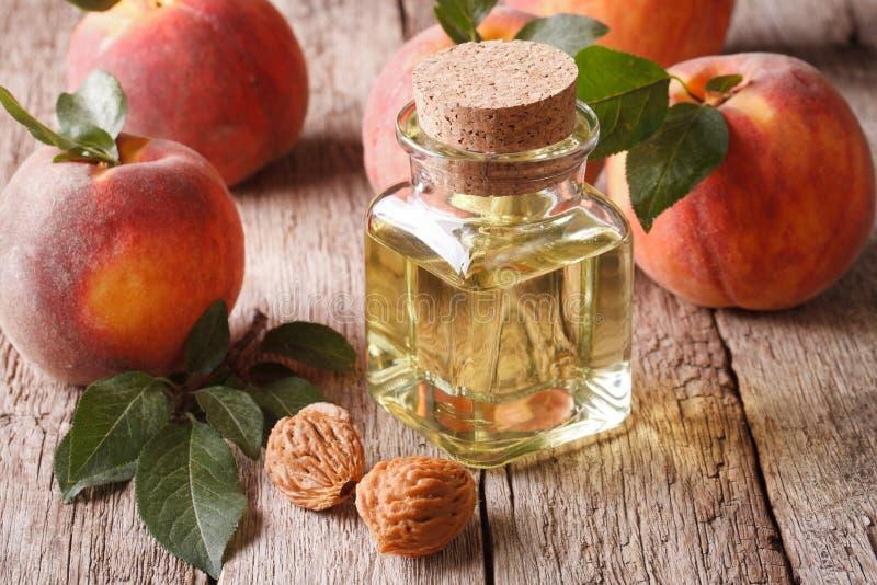 Natürliches frisches Pfirsichöl in einer Glasflaschennahaufnahme horizontal lizenzfreie stockfotografie