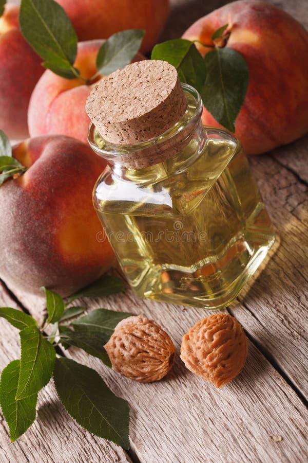 Natürliches frisches Pfirsichöl in einer Glasflaschennahaufnahme vertikal stockfotos