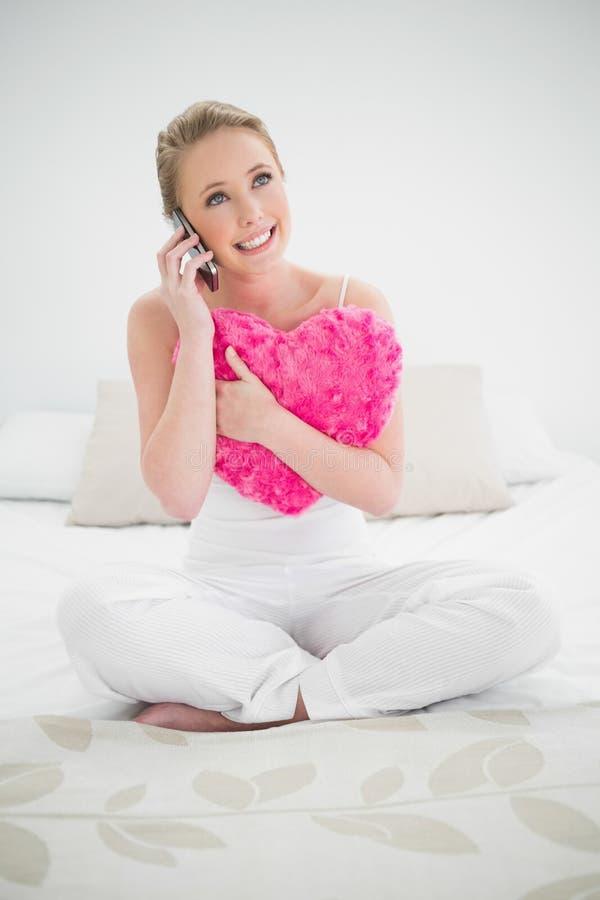 Natürliches glückliches blondes haltenes Herzkissen und -c$anrufen stockfotografie