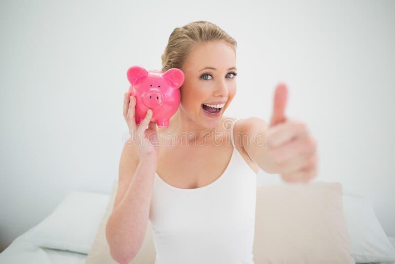 Natürliches glückliches blondes haltenes Sparschwein beim Sitzen auf Bett lizenzfreie stockbilder