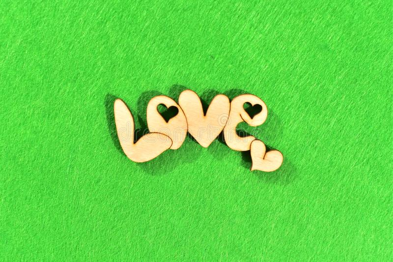 Natürliches hölzernes Wort 'Liebe 'auf grünem Hintergrund als Gras stockbild