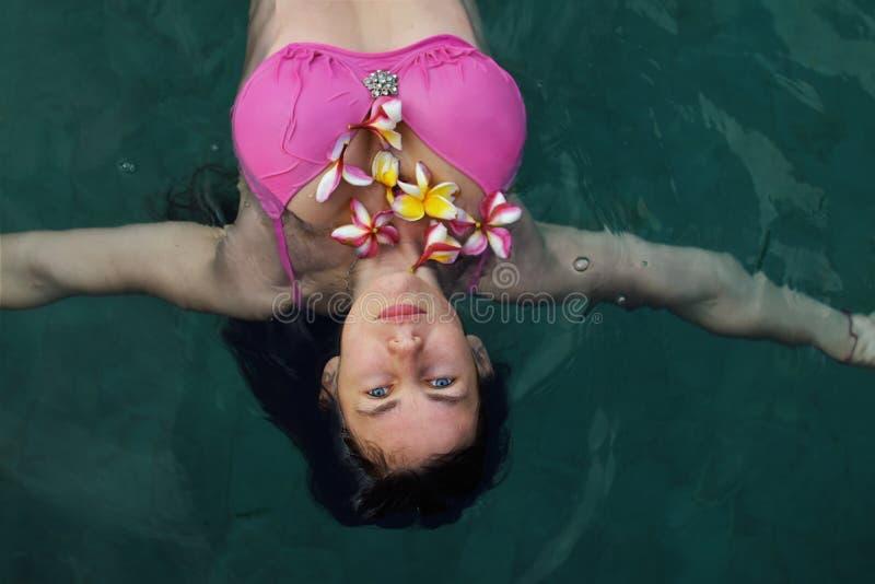 Natürliches Mädchen ohne Kosmetik, schöne junge Frauen mit Plumeriasblumen im blauen Swimmingpool lizenzfreie stockbilder