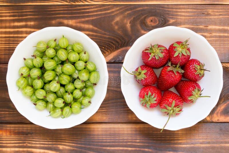 Natürliches organisches selbstgezogenes Produktkonzept Rote gereifte Erdbeeren und grüne Stachelbeeren in den weißen Schüsseln stockfotos