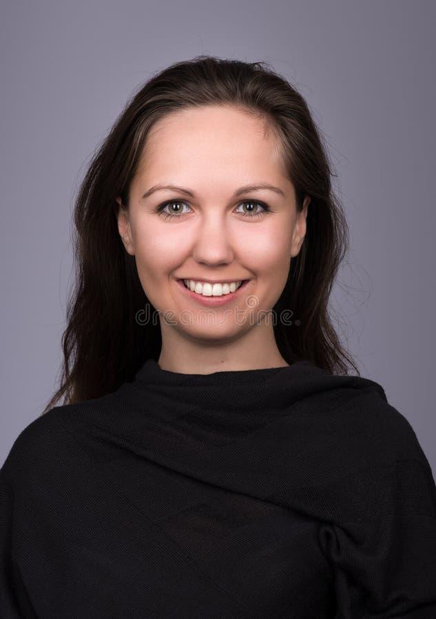 Natürliches Porträt der jungen Frau im Schwarzen auf einem dunkelgrauen Hintergrund lizenzfreie stockfotografie