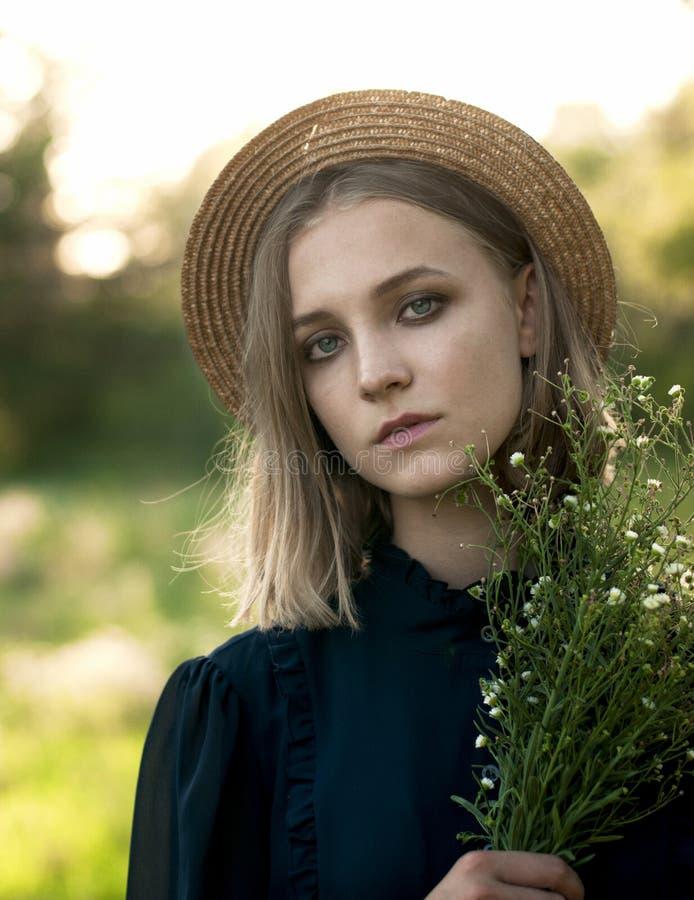 Natürliches Porträt eines Mädchens in einem Strohhut mit einem Blumenstrauß von wildem stockbild