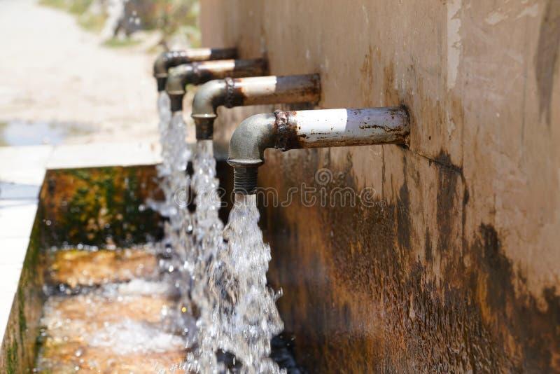 Natürliches Quellwasser, das von 4 Rohren fließt lizenzfreies stockfoto