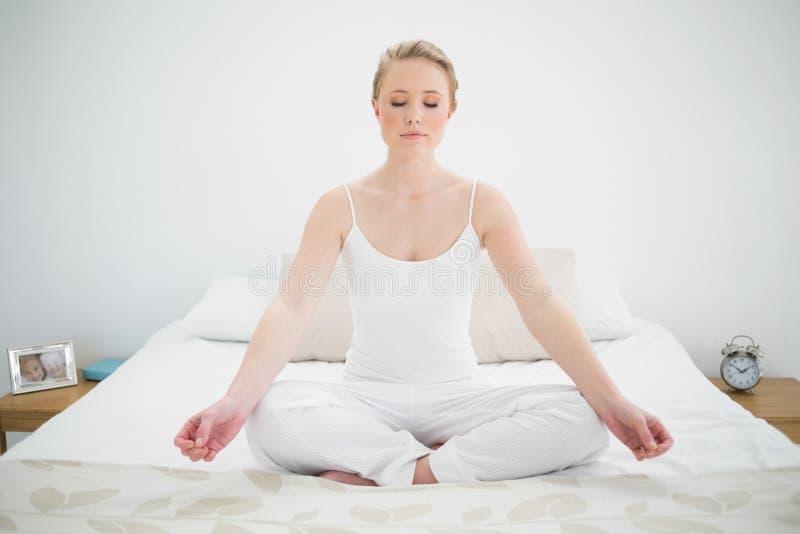 Natürliches recht blondes Meditieren auf Bett mit geschlossenen Augen stockfotos