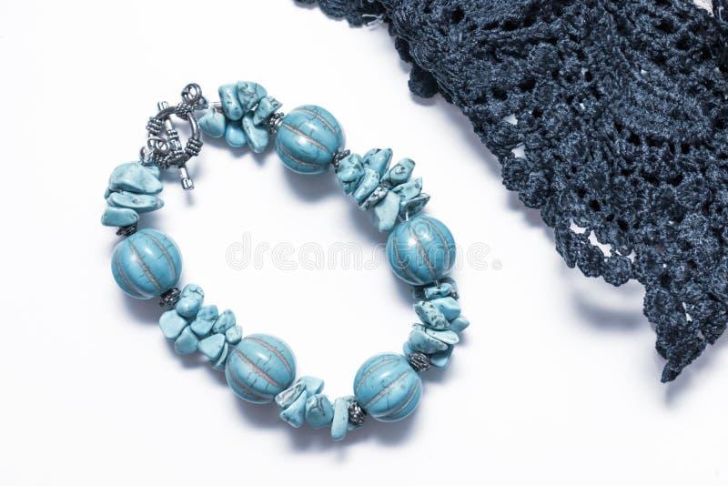 Natürliches Türkisarmband mit silbernem Verschluss und schwarze Gewebe textyle Spitze auf weißem Hintergrund, schönes blaues  lizenzfreie stockbilder