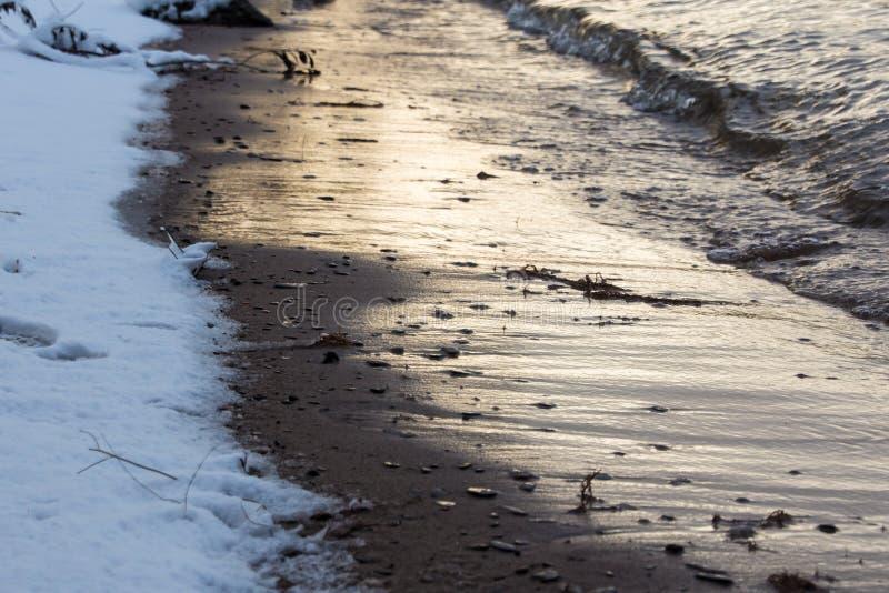Natürliches Ufer mit Steinen und Schnee im Winter lizenzfreie stockfotos