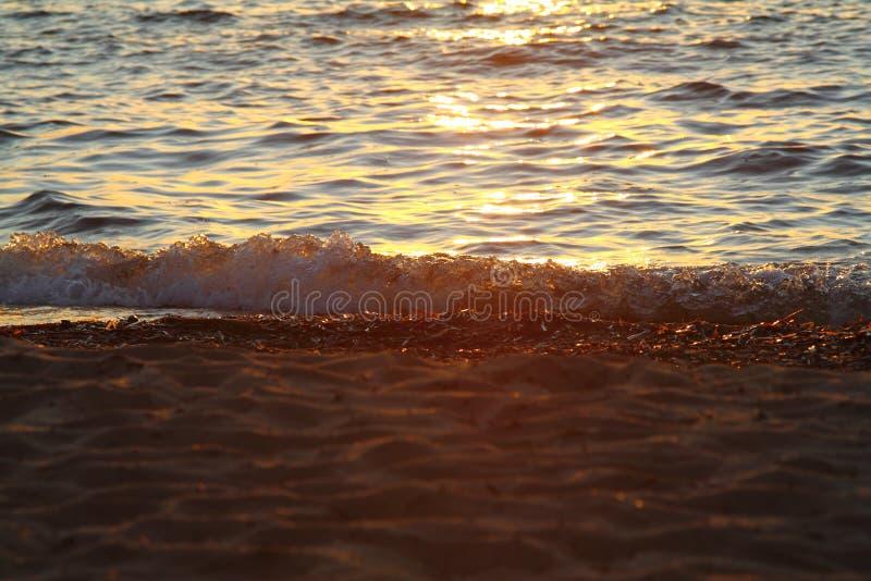 Nat overzees zand op strand tegen mooie gouden zonsondergang als achtergrond royalty-vrije stock foto
