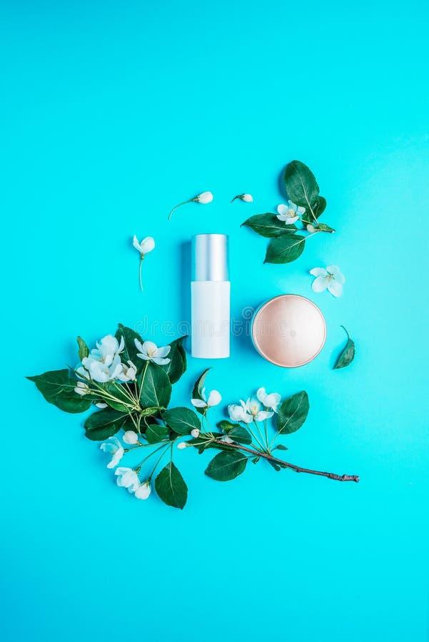 Nat?rliche organische Kosmetik auf blauem Hintergrund in einem Rahmen von Blumen, bl?hender Apfelbaum lizenzfreies stockfoto