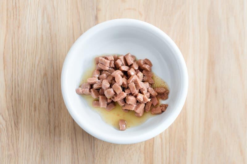 Nat voedsel voor katten en honden in een witte kom op houten vloer dichte omhooggaand stock foto