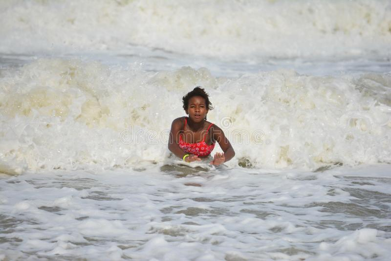 Natação afro-americano da menina em ondas de oceano fotos de stock
