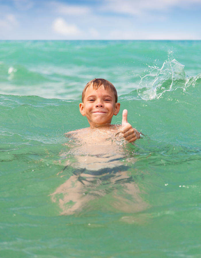 Natação alegre do menino no mar imagem de stock royalty free