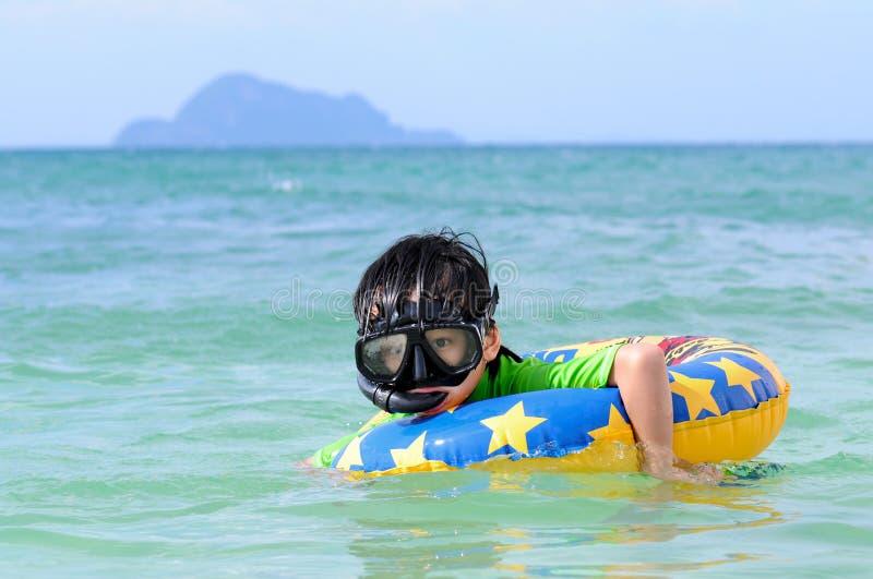 Natação bonito do menino no mar fotografia de stock