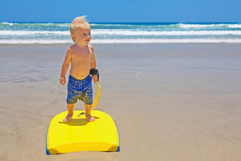 Natação da criança pequena com o bodyboard na praia da areia do mar foto de stock