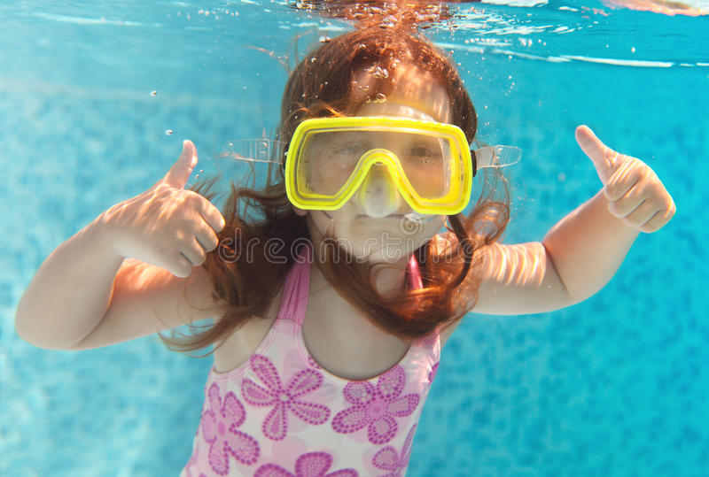 A natação da menina subaquática e sorriso imagens de stock