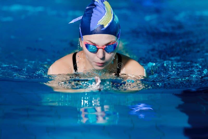 Natação da mulher com o chapéu da natação na piscina foto de stock