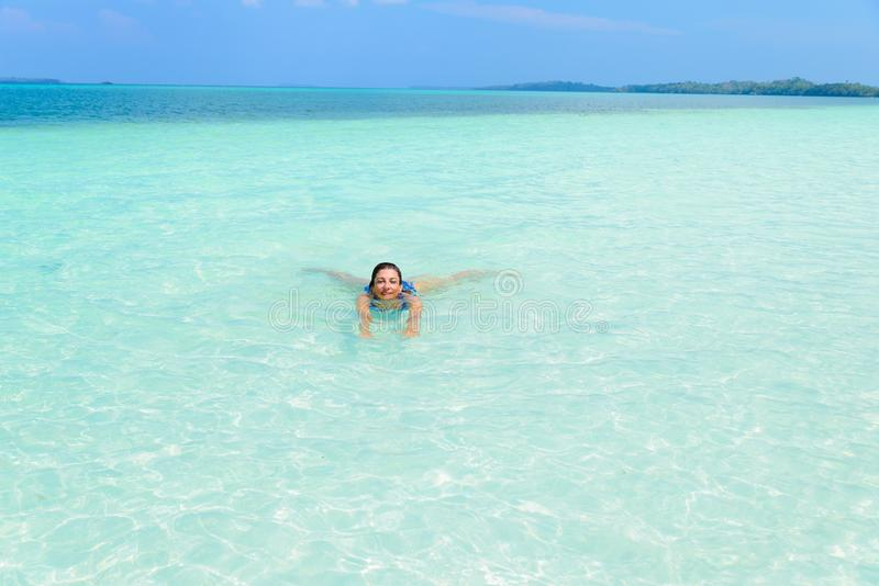 Natação da mulher na água transparente de turquesa do mar de Caraíbas Praia tropical em Kei Islands Moluccas, turista do verão fotografia de stock