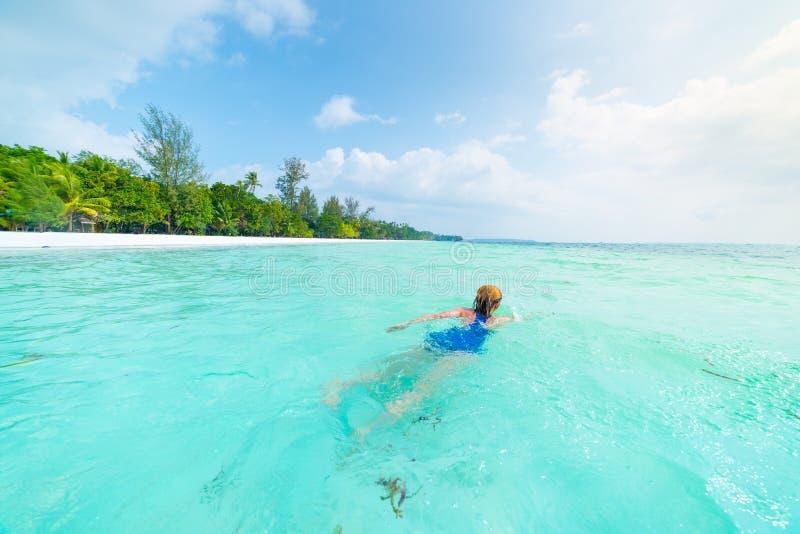 Natação da mulher na água transparente de turquesa do mar de Caraíbas Praia tropical em Kei Islands Moluccas, turista do verão foto de stock