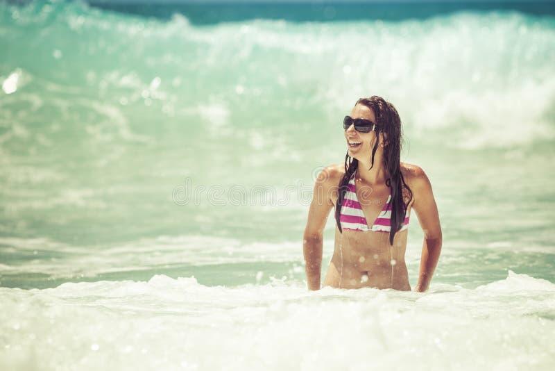 Natação da mulher na praia fotografia de stock