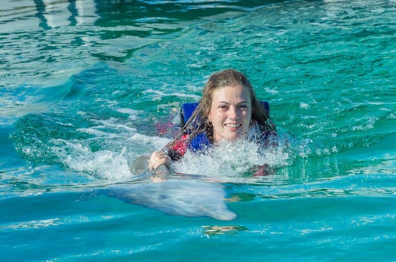 Natação de sorriso da mulher com o golfinho na água azul fotografia de stock royalty free