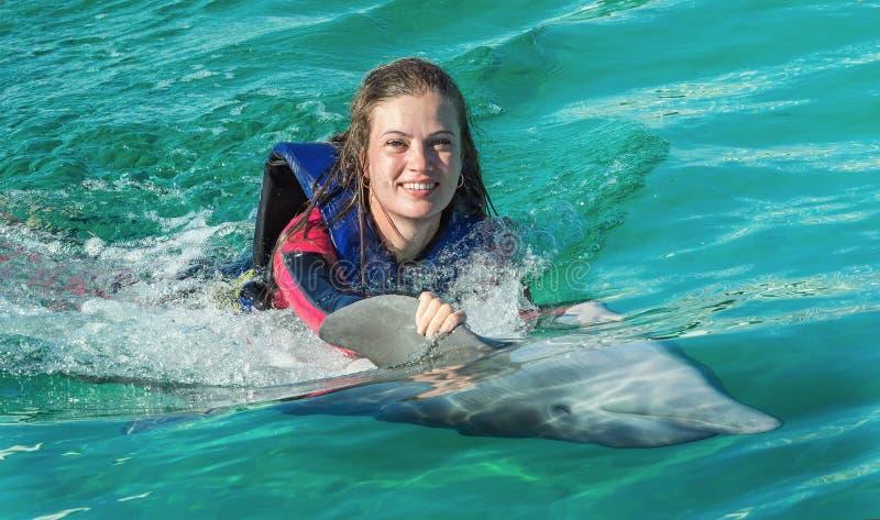 Natação de sorriso da mulher com o golfinho na água azul fotos de stock royalty free