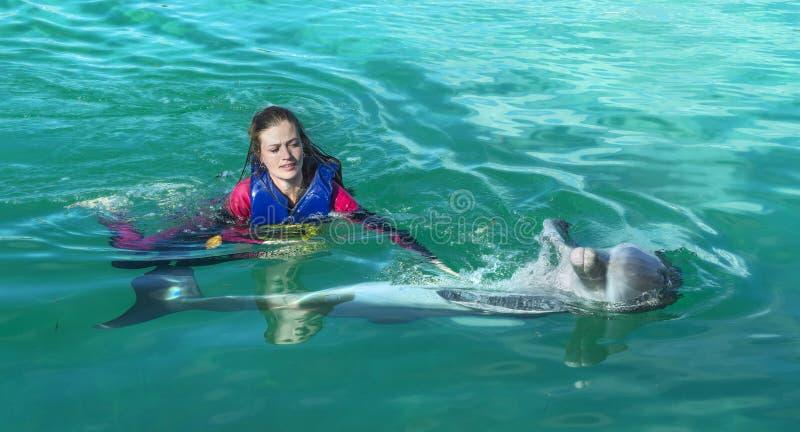 Natação de sorriso da mulher com o golfinho na água azul fotos de stock