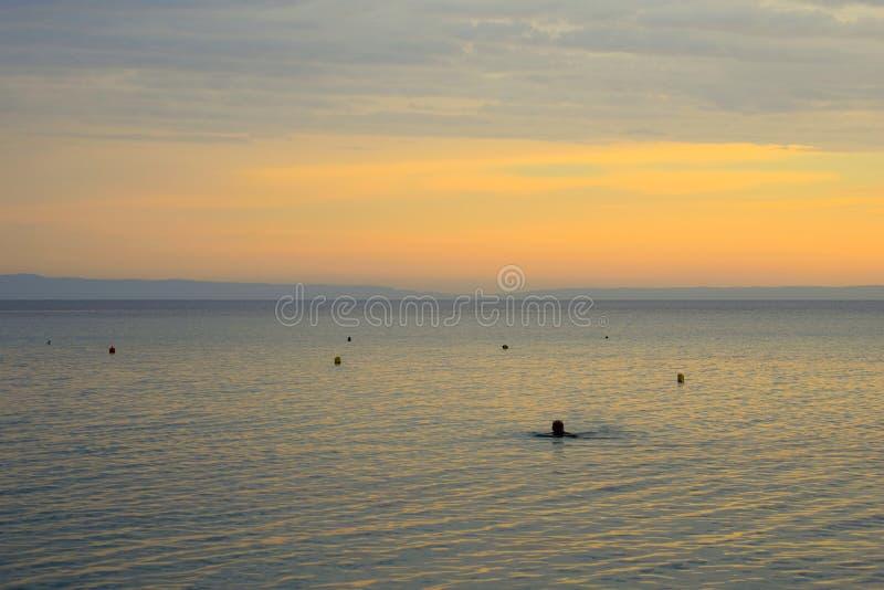Natação do homem no Mar Egeu calmo no nascer do sol fotos de stock