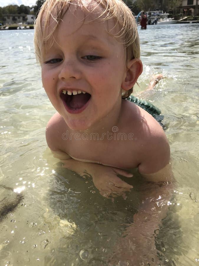 Natação do menino na água pouco profunda foto de stock