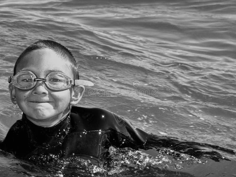 Natação do menino no oceano fotografia de stock royalty free
