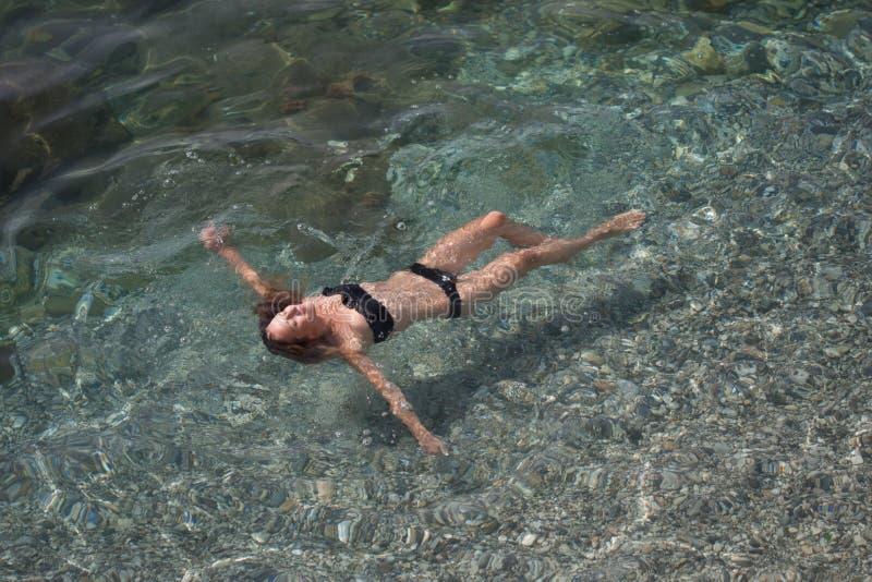 Natação fêmea nova apta na água do mar transparente fotos de stock