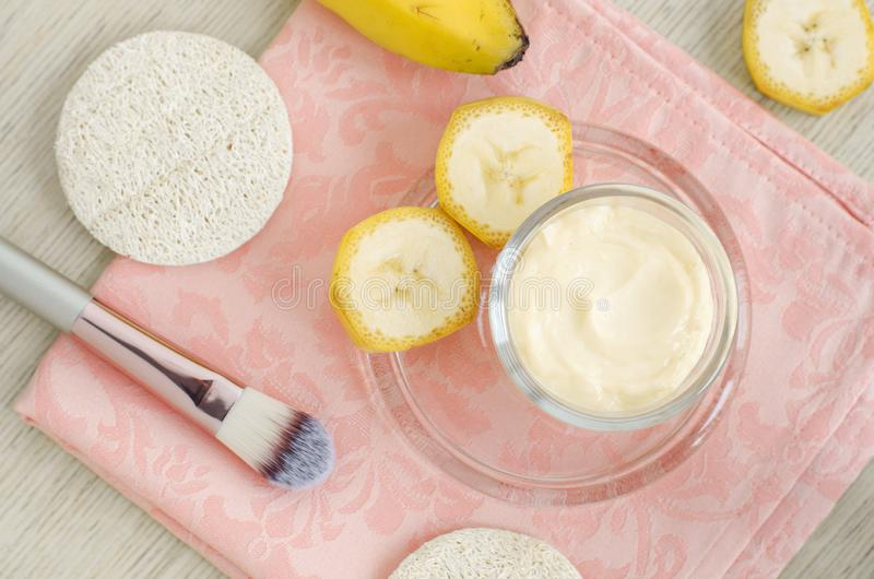 Nata hecha en casa de la mascarilla del plátano en el pequeño tarro de cristal y el cepillo cosmético Tratamientos y balneario de imágenes de archivo libres de regalías