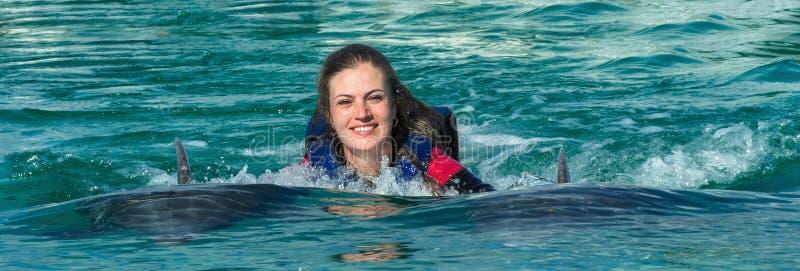 Nata??o de sorriso da mulher com os golfinhos na ?gua azul imagem de stock
