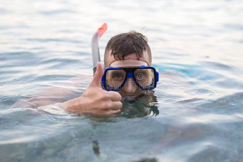 Nata??o do homem em uma m?scara para mergulhar e mostrar um sinal aproximadamente fotos de stock royalty free