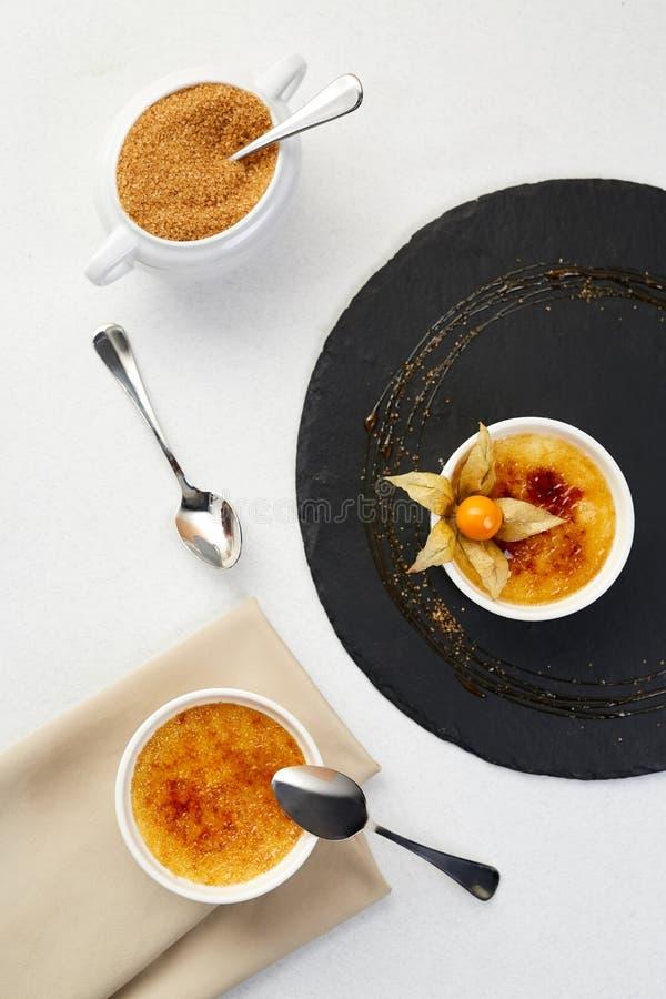 Nata quemada con el Physalis y el azúcar marrón Postre quemado de la nata con cofee en el esquisto negro fotos de archivo