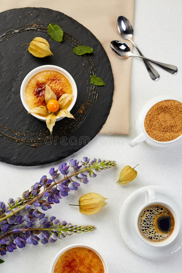 Nata quemada con el Physalis y el azúcar marrón Postre quemado de la nata con lavanda y café en el esquisto negro fotografía de archivo libre de regalías