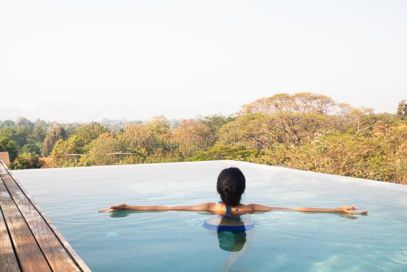 Natación asiática de la mujer y relajación en piscina en el top del tejado foto de archivo libre de regalías