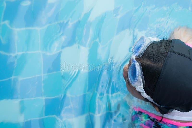 Natación asiática de la práctica de la niña para el partido en piscina Niña alegre en esta actividad Ella practica difícilmente e fotografía de archivo
